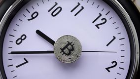 Bitcoin coins on the watch dial. Bitcoin spins on the dial rotation stock video footage