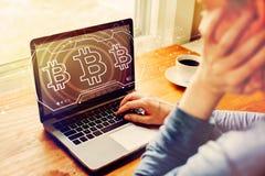 Bitcoin com o homem que usa um port?til imagens de stock royalty free