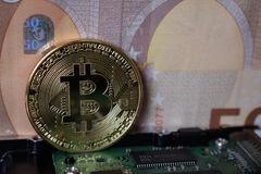 Bitcoin on a computer board and against the background of a euro banknote stock photography