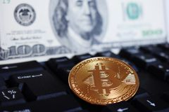 Bitcoin on a computer keyboard on the background of the US dollar, the symbol of electronic virtual money and the concept of stock photos