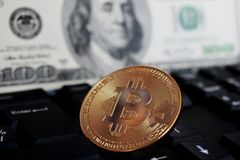 Bitcoin on a computer keyboard on the background of the US dollar, the symbol of electronic virtual money and the concept of royalty free stock photo