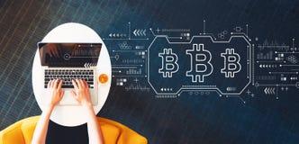 Bitcoin con la persona que usa un ordenador portátil imagen de archivo