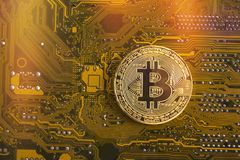 Bitcoin concept - gold coin, computer circuit Board with bitcoin processo. R and microchips. Electronic currency, Internet Finance Royalty Free Stock Photography