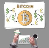 Bitcoin concept placed on a desk. Male hands using tablet in front of bitcoin concept royalty free stock photos