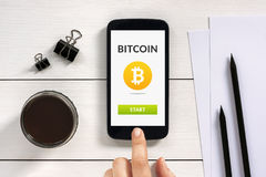 Bitcoin concept on smart phone screen with office objects. On white wooden table. All screen content is designed by me. Flat lay Royalty Free Stock Image
