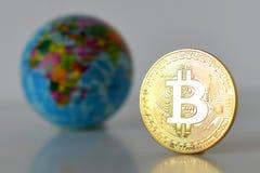 Bitcoin concept. World economy concept. New world currency.Golde. Bitcoin concept. World economy concept. New world currency. Golden coin bitcoin and globe Royalty Free Stock Image