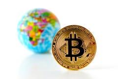 Bitcoin concept. World economy concept. New world currency.Golde. Bitcoin concept. World economy concept. New world currency. Golden coin bitcoin and globe Royalty Free Stock Photo