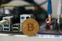 Bitcoin contro lo sfondo della scheda madre nello scaffale per l'estrazione mineraria cripto di valuta Fotografia Stock