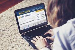 Bitcoin converter website in a laptop screen while woman trades bitcoin price. Stock Photos