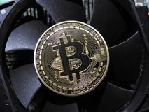 Bitcoin on cooling fan. Closeup of bicoin resting on top of cooling fan Royalty Free Stock Photo