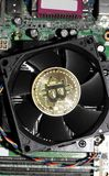 Bitcoin on cooling fan. A physical  bitcoin on a cooling fan on a computer motherboard Stock Images
