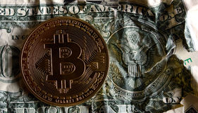 Bitcoin on US seal Crushed dollar banknote. Bitcoin on Crushed dollar banknote against the seal of USA.Concept of  Monetary system collapse Royalty Free Stock Images