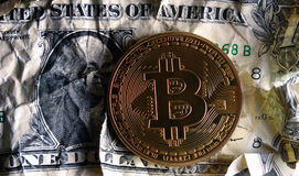 Bitcoin on Crushed dollar banknote. Concept of  Monetary system collapse Stock Photos