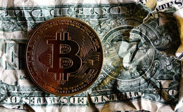 Bitcoin on Crushed dollar banknote. Concept of  Monetary system collapse Stock Images