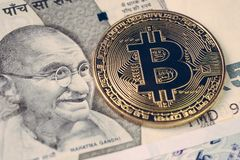 Bitcoin crypto currency banned in India concept, closed up shot. Of golden physical coin with B alphabet Bit coin sign on Indian rupee banknotes stock image