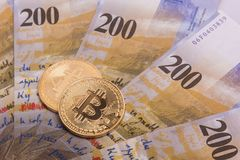 Bitcoin crypto currency coin over swiss francs bank notes Royalty Free Stock Image