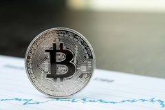 Bitcoin crypto currency concept, silver physical bitcoin coin wi. Th B sign on blue pricing market price graph line printed document stock photo