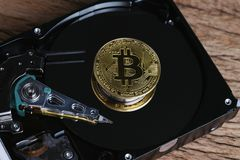 Bitcoin crypto currency digital money concept, shiny golden physical bitcoin coin with B sign on computer disk drive or hard drive. Data in low key on wooden stock photography