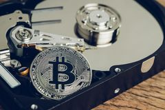 Bitcoin crypto currency digital money concept, shiny metal physical bitcoin coin with B sign on computer disk drive or hard drive. Storage data in low key on stock image
