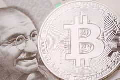 Bitcoin crypto currency, digital money in India concept, closed up shot of physical coin with B sign alphabet on face of Indian. Rupee banknote stock photography