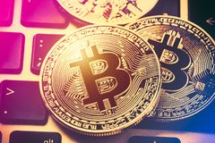 Bitcoin cryptocurrency coins on laptop keyboard. Close up toned image. Crypto currency - electronic virtual money for web banking stock photography