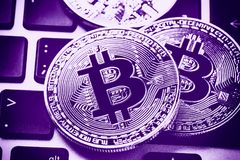 Bitcoin cryptocurrency coins on laptop keyboard. Close up Ultraviolet toned