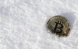 Bitcoin Cryptocurrency en nieve, en el fondo El concepto de trabajar independientemente, la bolsa de acción Bitcoin del oro en fr Fotografía de archivo libre de regalías