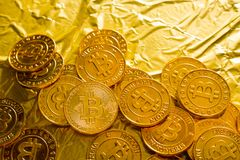 The Bitcoin cryptocurrency in gold texture image background. stock image