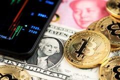 Bitcoin Cryptocurrency monety na dolara amerykańskiego i Juan walucie Porcelanowi banknoty obok telefonu komórkowego pokazuje can obrazy stock