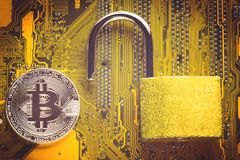 Bitcoin cryptocurrency with opened padlock on computer motherboard. Crypto currency - electronic virtual money for web banking and. Bitcoin cryptocurrency with Royalty Free Stock Images