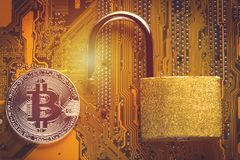 Bitcoin cryptocurrency with opened padlock on computer motherboard. Crypto currency - electronic virtual money for web banking and. Bitcoin cryptocurrency with Stock Image