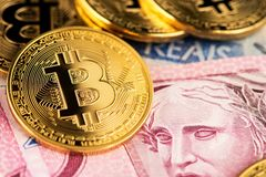 Bitcoin cryptocurrency virtual money on Brazilian Real money banknotes. stock image