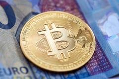 Bitcoin cryptocurrency, złocista moneta, kłamstwa na euro rachunku fotografia royalty free