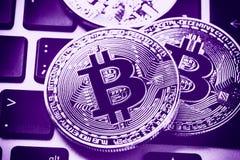 Bitcoin cryptocurrencymynt på bärbar datortangentbordet Slut upp tonad Ultraviolet Arkivfoto