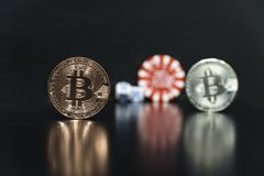 Bitcoin cubes casino chips. Bitcoins on a black background with game cubes. Bitcoins on a black background with game cubes stock image