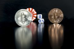 Bitcoin cubes casino chips. Bitcoins on a black background with game cubes. Bitcoins on a black background with game cubes royalty free stock image