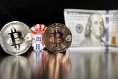 Bitcoin cubes casino chips. Bitcoins on a black background with game cubes. Bitcoins on a black background with game cubes royalty free stock images