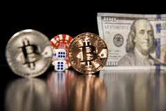 Bitcoin cubes casino chips. Bitcoins on a black background with game cubes. Bitcoins on a black background with game cubes stock photo