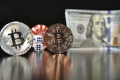 Bitcoin cubes casino chips. Bitcoins on a black background with game cubes. Bitcoins on a black background with game cubes stock photography
