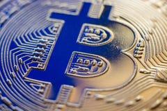 Bitcoin coin currency closeup on blue backlight. Bitcoin currency DOF on blue glass background. Gold metal curency symbol macro photo closeup stock photos