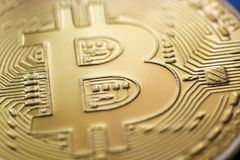 Bitcoin monet coin currency closeup. Bitcoin currency DOF on blue glass background. Gold metal curency symbol macro photo closeup stock images