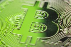 Bitcoin monet coin currency closeup on green light. Bitcoin currency DOF on blue glass background. Gold metal curency symbol macro photo closeup stock images