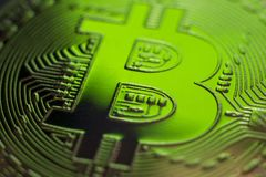 Green color light on Bitcoin monet coin. Bitcoin currency DOF on blue glass background. Gold metal currency symbol macro photo closeup stock images