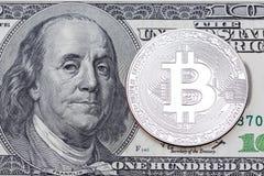 Bitcoin d'argento su cento dollari di banconota Fotografia Stock