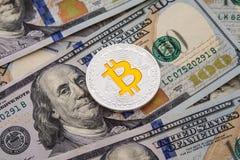 Bitcoin d'argento sulle banconote dei dollari americani Concetto di estrazione mineraria Immagini Stock