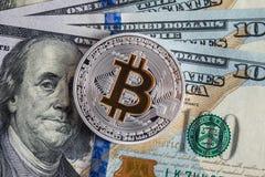 Bitcoin d'argento sulle banconote dei dollari americani Concetto di estrazione mineraria Fotografie Stock Libere da Diritti