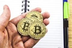 Bitcoin d'or dans une main du ` s d'homme Symbole d'une nouvelle devise virtuelle illustration 3D Photos stock
