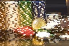 Bitcoin d'or devant des piles de puces de jeu vert-bleu et rouges blanches Images stock