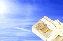 bitcoin d'E-devise sur une boîte de papier dans un style ancien, sur un fond de ciel bleu Photo libre de droits