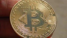 Bitcoin da moeda de ouro na mão de um homem novo vídeos de arquivo